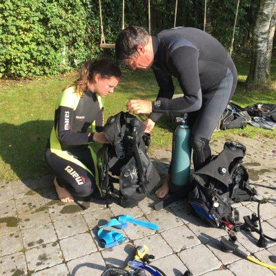 Divemaster helpt met opbouwen duikset