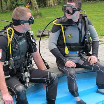 2 duikers in volle uitrusting aan de rand van zwembad