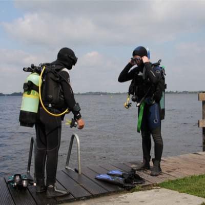 2 duikers met complete uitrusting aan de rand van het water