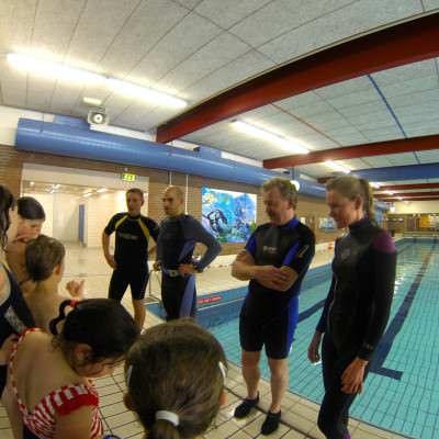 kinderen en instructeurs aan de rand van het zwembad